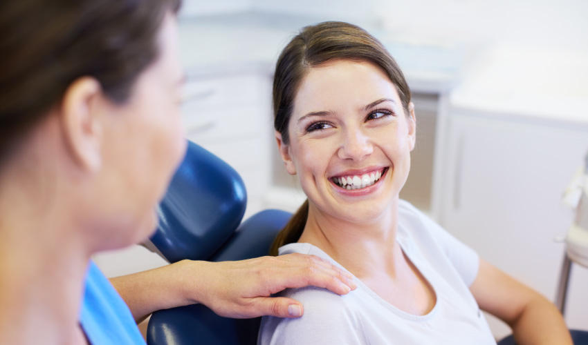 A brunette woman in a dental chair smiles after receiving Zircteeth replacement teeth