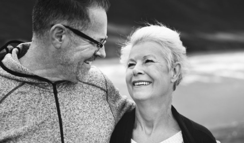Elderly couple smile at each other after receiving dental restorations