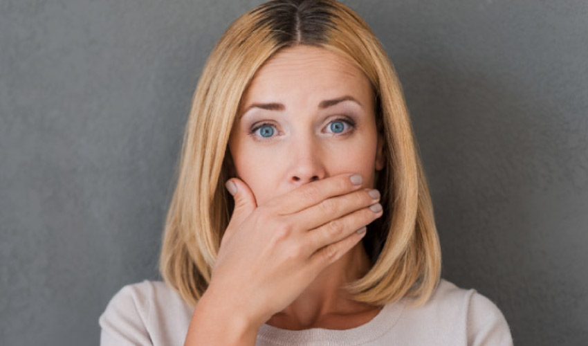 woman covering her mouth because of bad breath